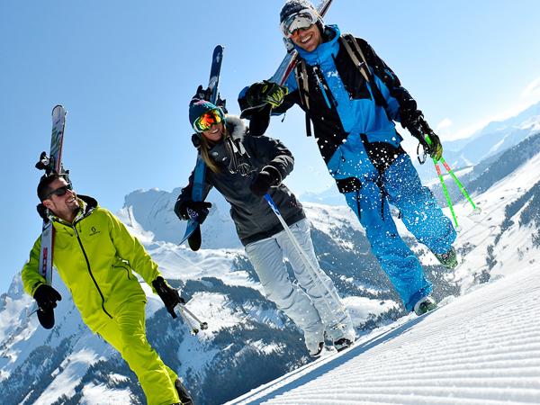 Skiers, blue sky, groomed pistes
