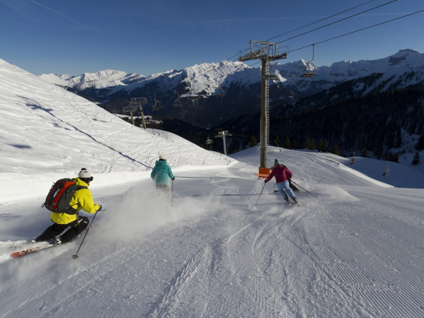 Skiers skiing fast on-piste