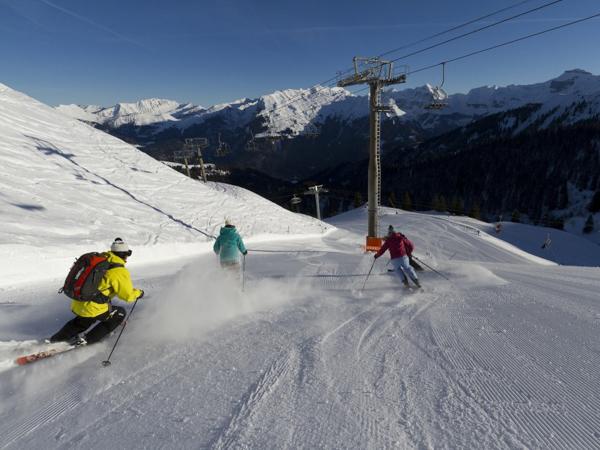 Skiers skiing fast on-piste