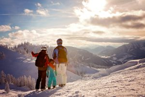 Family in ski clothing on a mountain on a sunny day