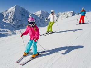 Children and mum skiing in the mountains
