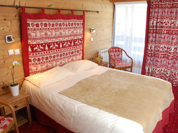 Hotel Chemenaz comfortable bedroom in traditional mountain style